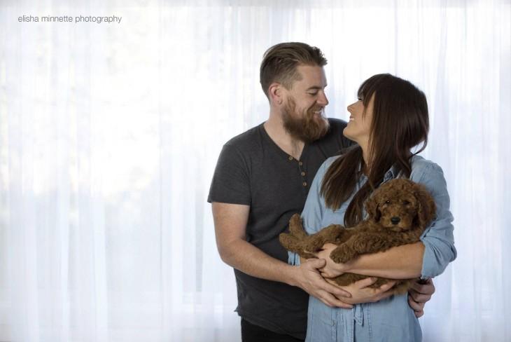 Pareja de esposos abrazados y la mujer con un perro recostado en sus brazos