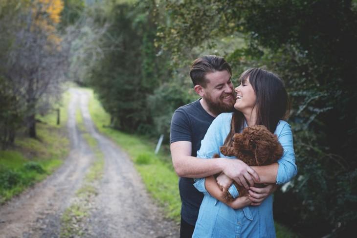 Pareja de esposos cargando a un perro entre sus brazos