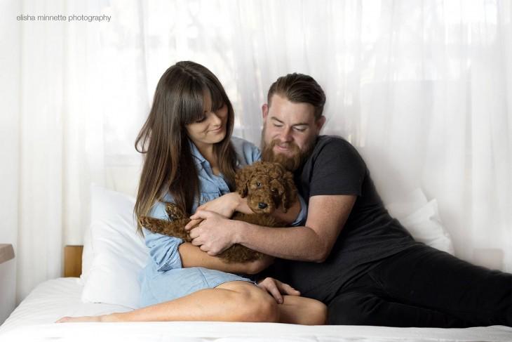 Un matrimonio recostados en la cama sosteniendo en sus brazos a su pequeño y adorable cachorro