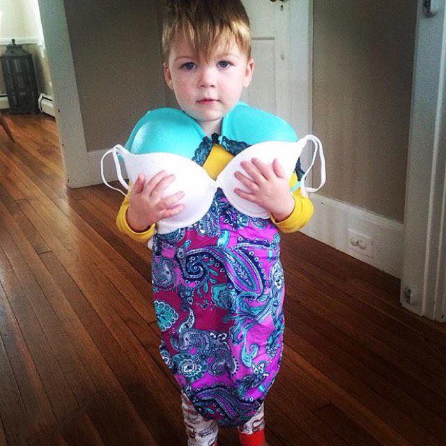 Niño parado a la mitad de un pasillo con dos pares de brasiere en su pecho