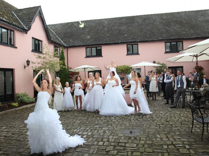 Chica lanzando el ramo a otras chicas con grandes vestidos de novia