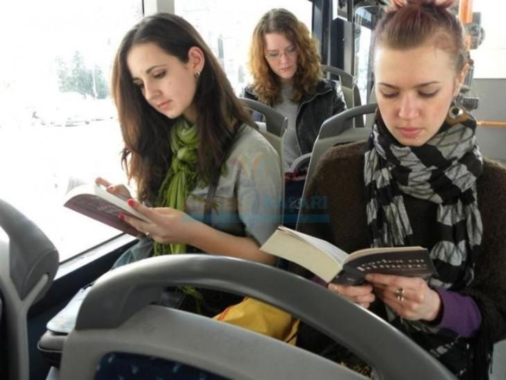 Chicas leyendo un libro en el transporte público en Rumania