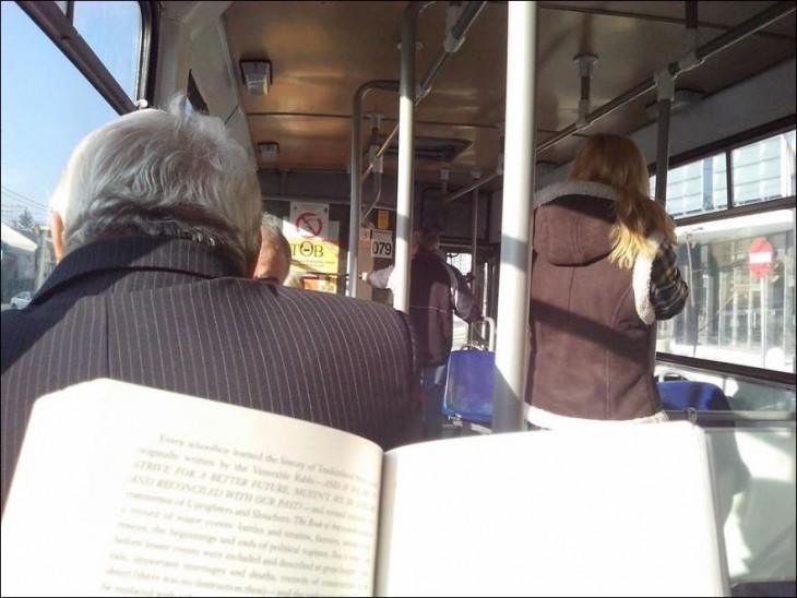 Espalda de una persona en el autobús y una persona con un libro en sus manos