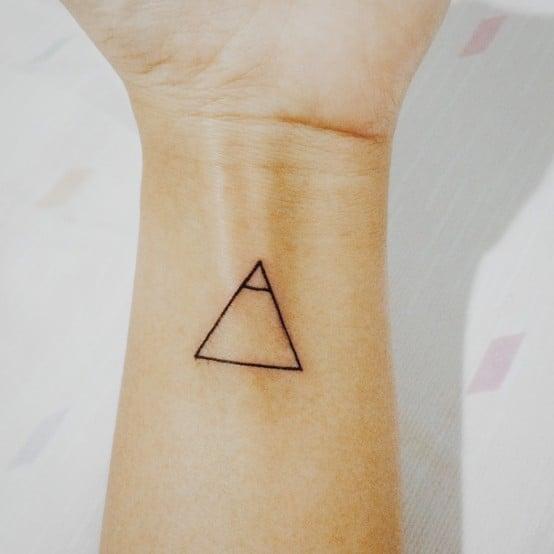Tatuaje de un triángulo en la muñeca de la mano