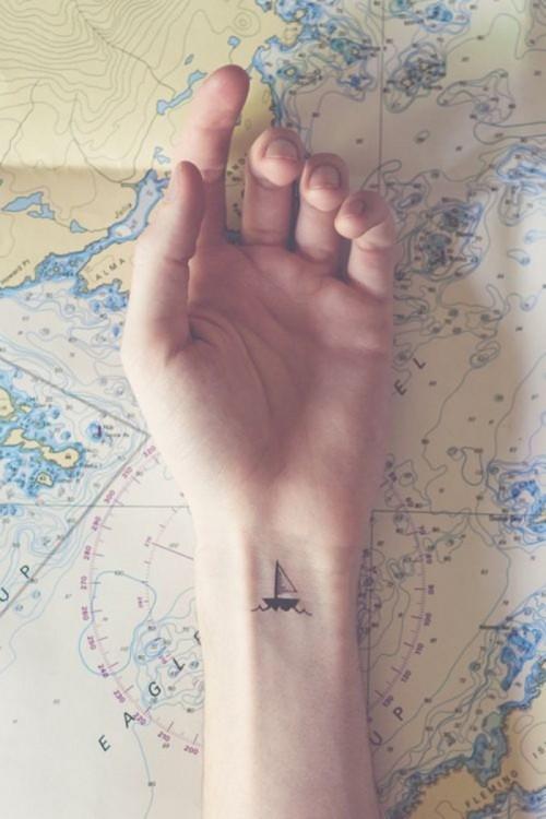 Tatuaje en la muñeca de una mano con el diseño de un pequeño barco navegando