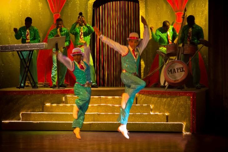 Dominicanos en un escenario tocando y bailando música de Merengue