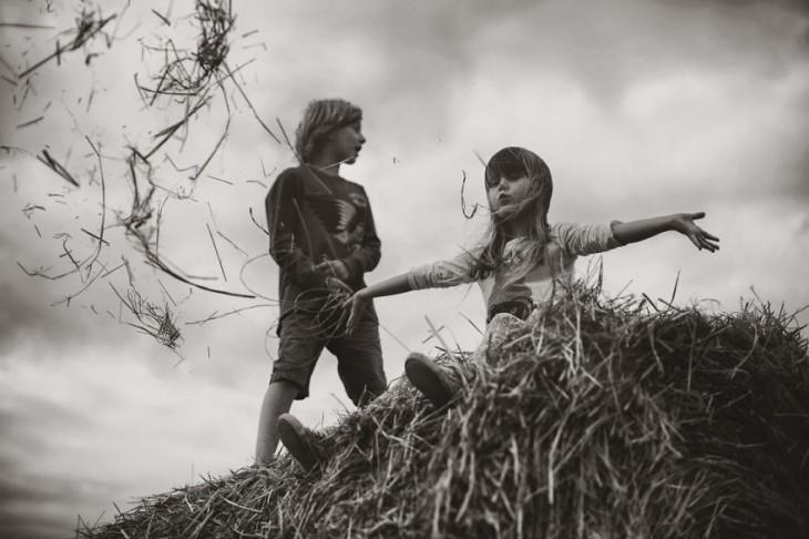 niña sentada en una paja a punto de aventarse junto a un niño