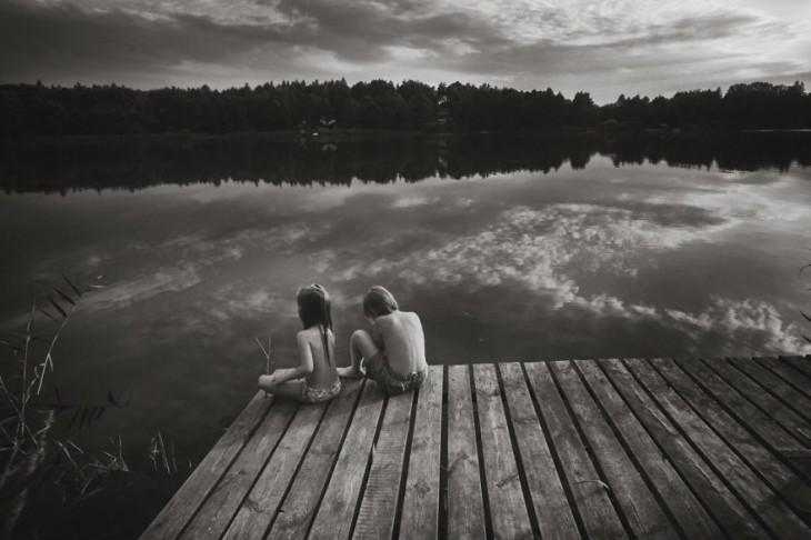 una niña y un niño sentados en un puente a la orilla de un lago