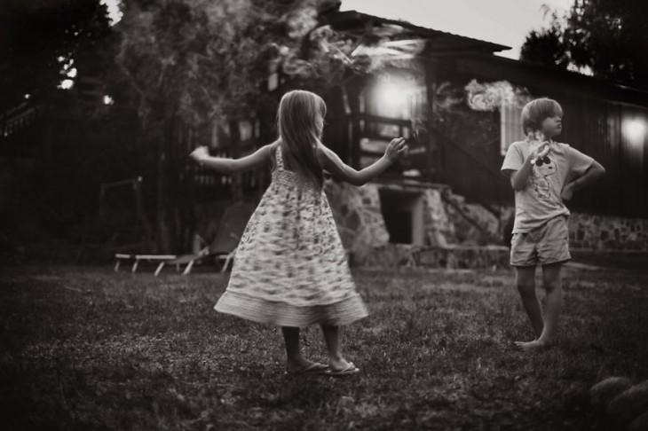 niña dándose vueltas frente a un niño en el jardín de una casa