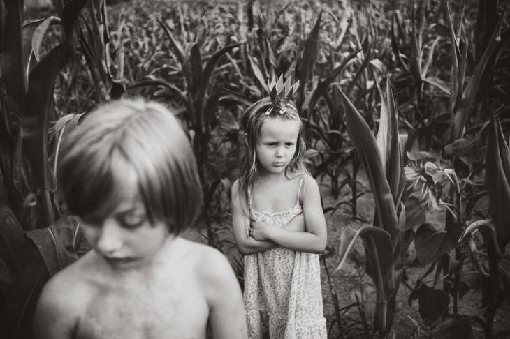niña con una corona y los brazos cruzados detrás de un niño en medio de unos matorrales