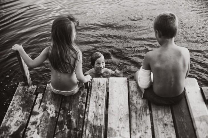 una niña y un niño sentados en un puente viendo a un niño que esta dentro de un lago