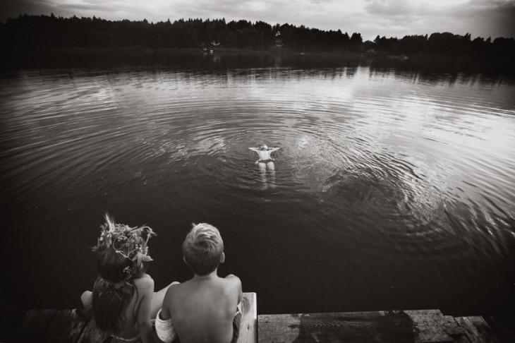 niño nadando en un lago mientras dos niños sentados en un muelle lo ven