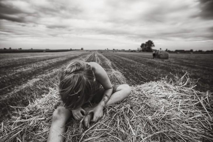 Niño sentado sobre un montón de paja tocando un pie