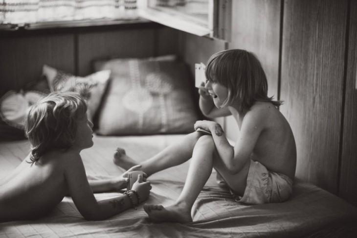 Dos niños jugando y platicando encima de una cama