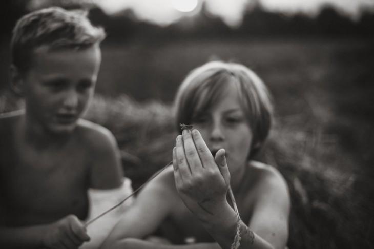 dos niños mirando la mano de uno de ellos con un grillo en su dedo
