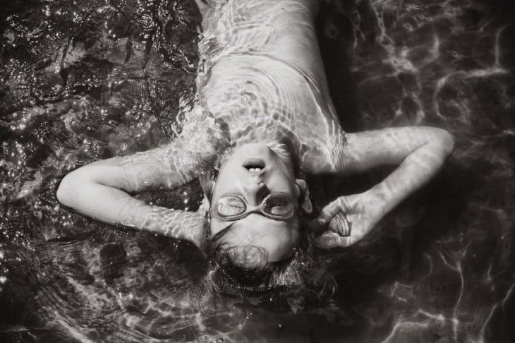 niña acostada sobre el agua con los ojos cerrados