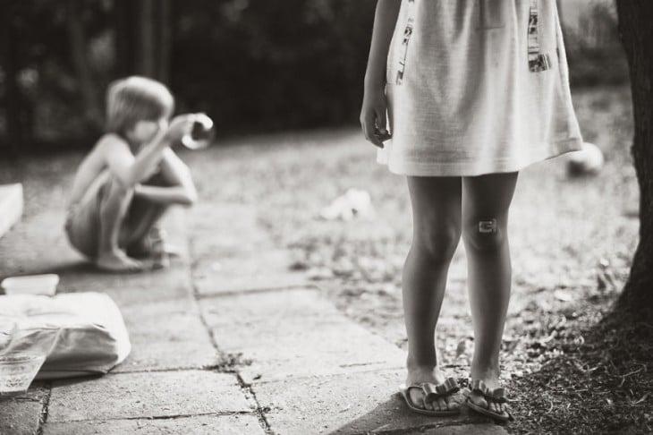 Fotografía de un niño sentado en el suelo con una niña parada