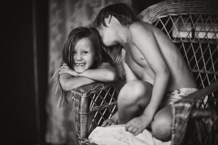 niño sentado en una silla dando un beso en la cabeza a una niña
