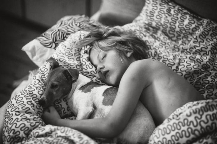 Niño acostado dormido abrazado de un perro