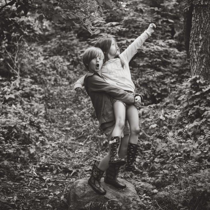 Niño sobre una piedra cargando a una niña