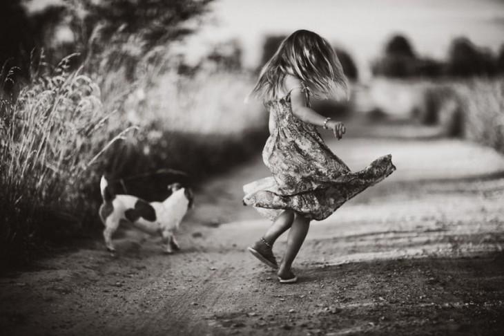 Niña dándose vueltas junto a un perro en medio de un camino en el campo