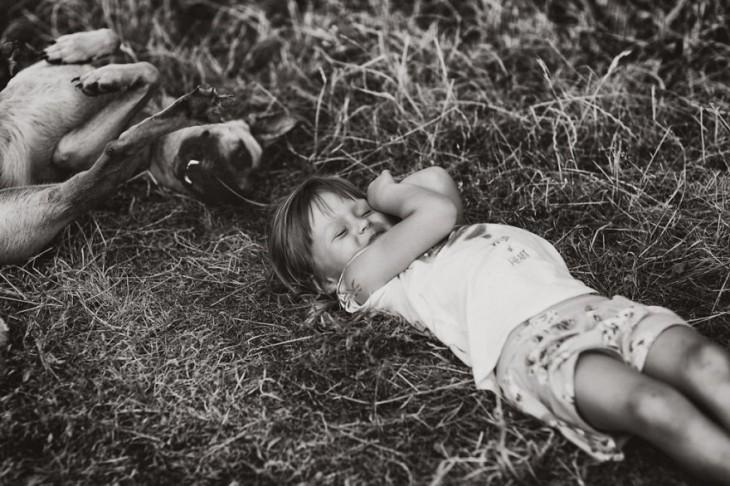 Niña acostada en el suelo con un perro a un lado de ella