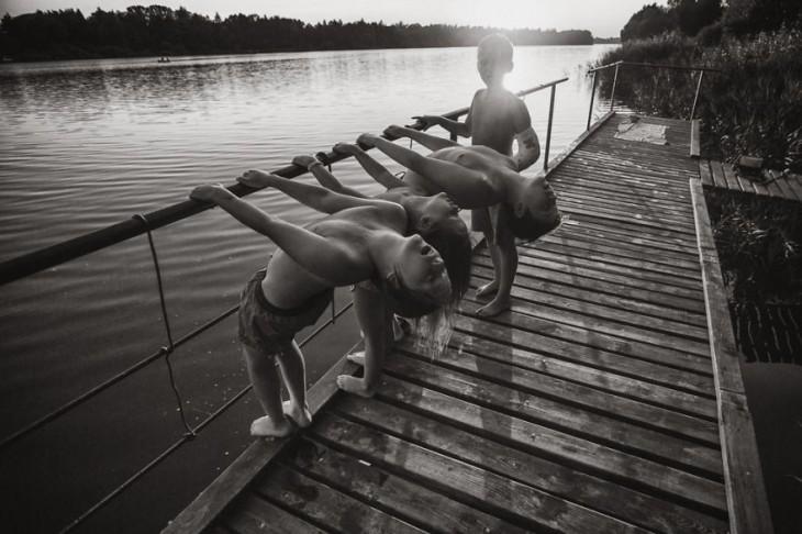 Niños en un puente colgados de un tubo inclinándose hacia atrás