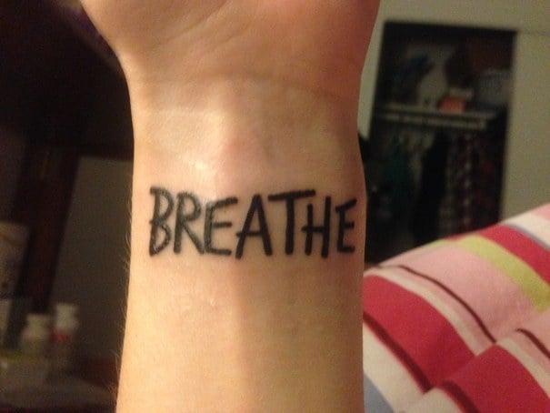 "tatuaje de la frase ""Breathe"" en la muñeca de un chico"