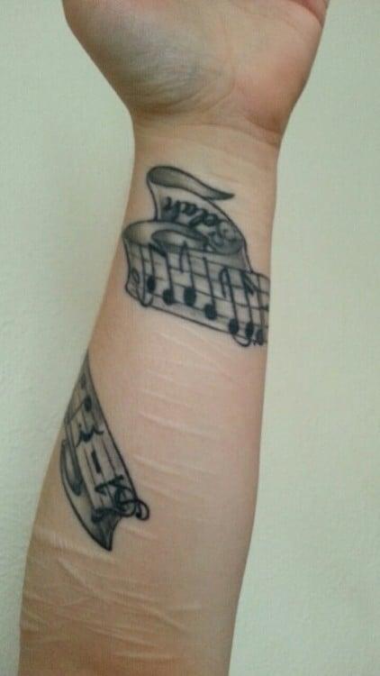 Brazo de una persona con un tatuaje con la forma de un pentagrama de una canción