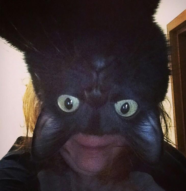 mujer con la cara del gato encima de su rostro