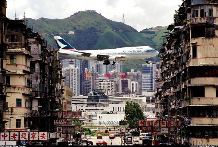 avion atravesando los edificios de hong kong