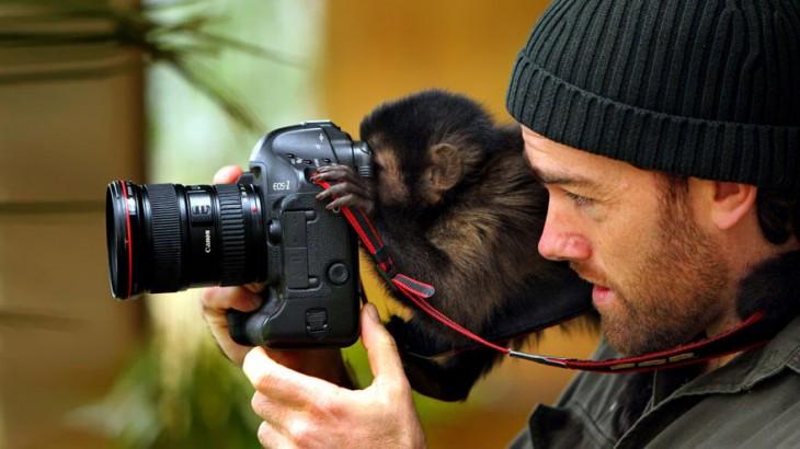 Fotógrafo junto a un pequeño chango detrás de una cámara tomando una foto