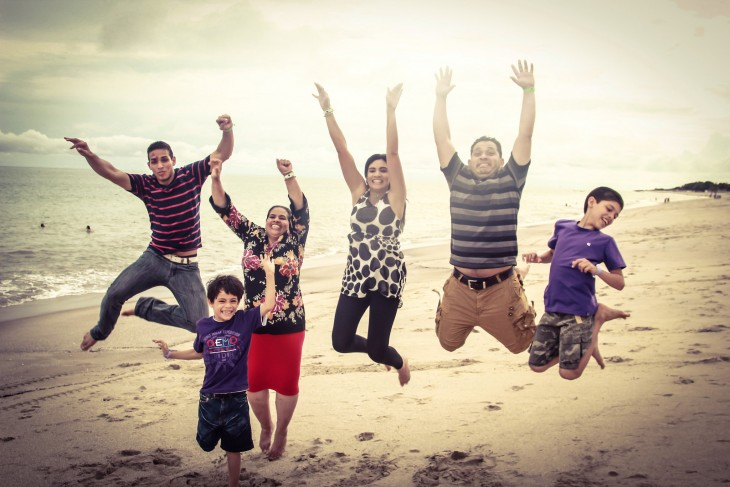 familia panameña saltando frente a la playa