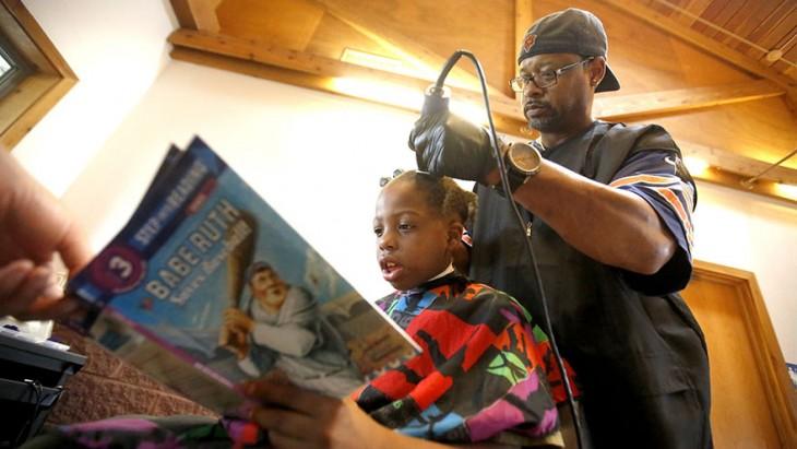 peluquero corta cabello a niños a cambio de que le lean una historieta