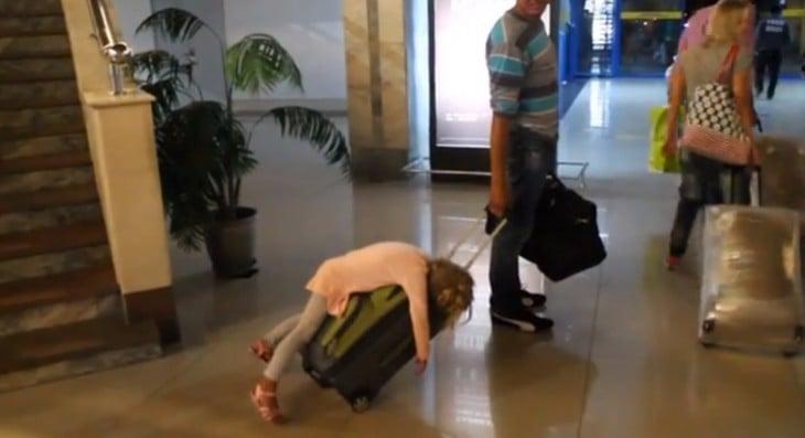 NIÑA DORMIDA SOBRE LA MALETA DE SU PAPA EN EL AEROPUERTO