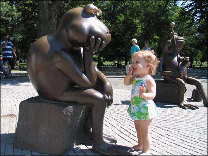 niña platicando con una rana estatua