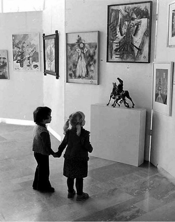 niños viendo una escultura de los caballos