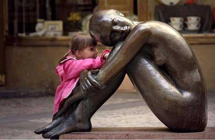 niña contandole un secreto a la estatua