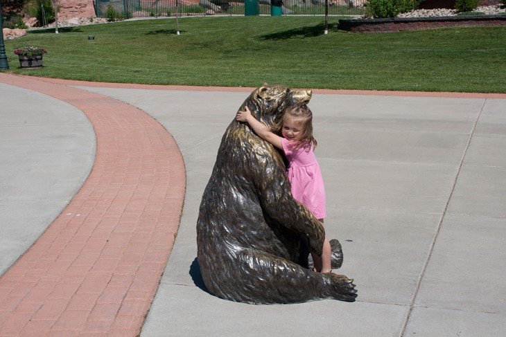niña abranzando ia un oso de estatua