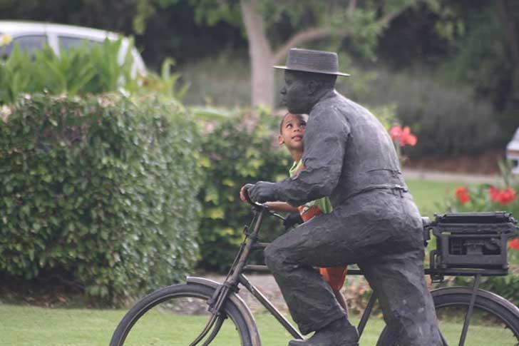 niño montado en una bicicleta junto a una estuatua