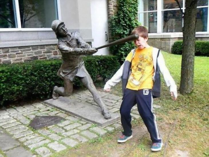 niño simulando que la estatua le pega con un bate