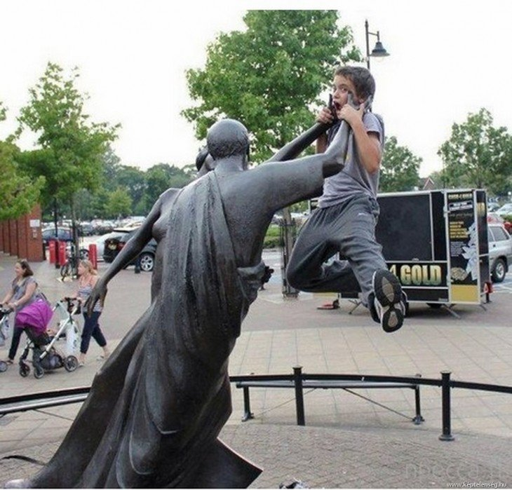 niño simulando que la estatua lo ahorca