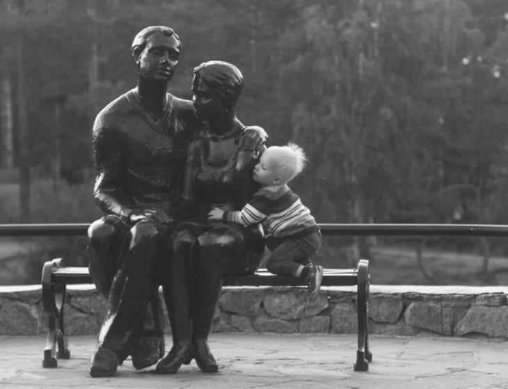niño abranzando a una pareja de estatuas