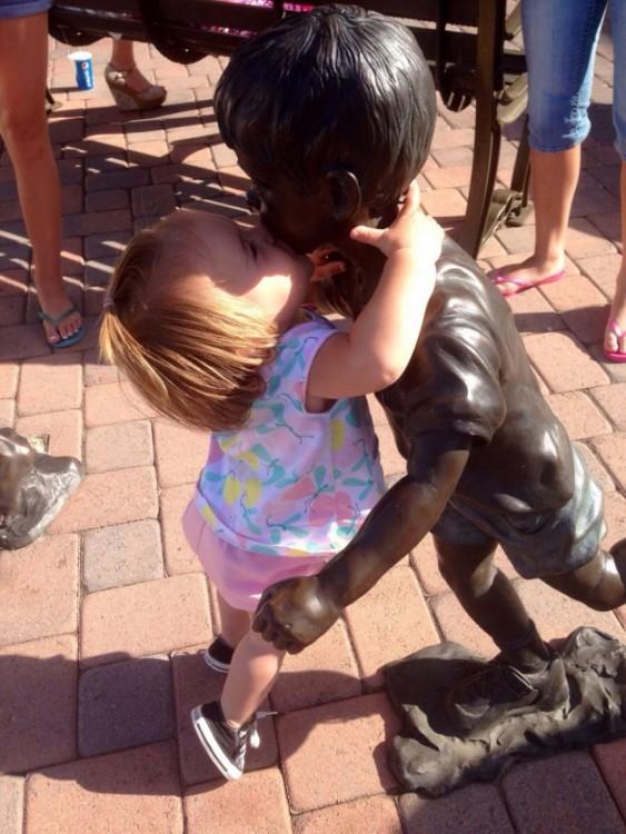 niña le roba un beso a la estatua