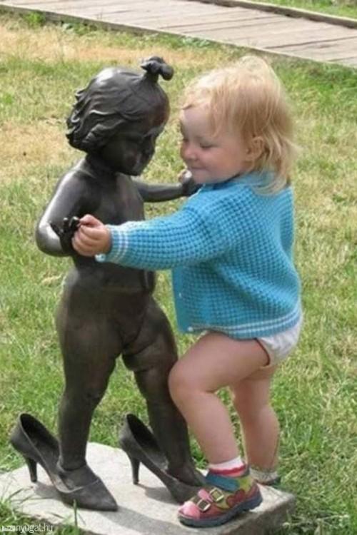 niña bailando con una estatua de niña con zapatillas