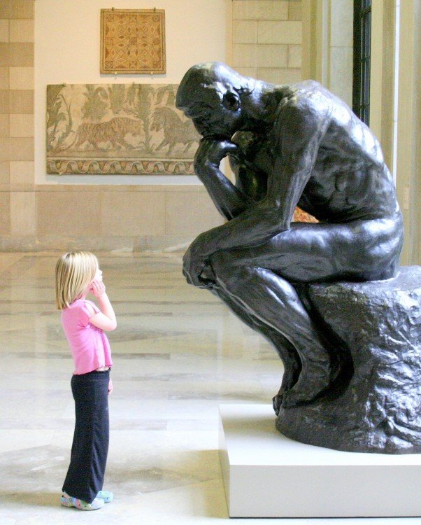 niña imitando la pose del pensador