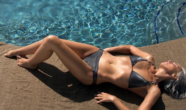 Modelo francesa de 59 años tomando el sol a un costado de una alberca