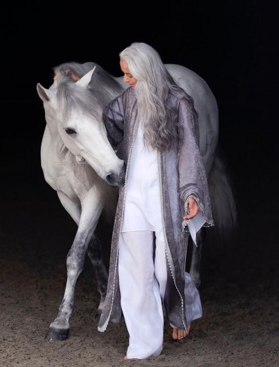 Rossi la modelo francesa de 59 años caminando junto a un caballo blanco