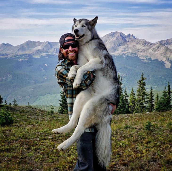 Kelly Lund cargando a su perrolobo Loki en un paisaje natural cerca de unas montañas