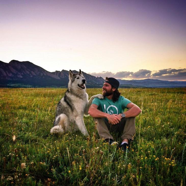 Loki el perro lobo colocando su pata sobre su amo Kelly Lund